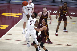 Southern Illinois guard Lance Jones (5) shoots over Loyola Chicago's Lucas Williamson, right as Cameron Krutwig, back, watches during the first half of an NCAA college basketball game Saturday, Feb. 27, 2021, in Chicago. (AP Photo/Shafkat Anowar)