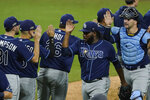 Tampa Bay Rays pitcher Diego Castillo is congratulated by his teammates after Game 3 of a baseball American League Championship Series against the Houston Astros, Tuesday, Oct. 13, 2020, in San Diego. The Rays defeated the Astros 5-2 to lead the series 3-0 games. (AP Photo/Ashley Landis)