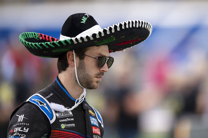 Daniel Suarez (99) walks to his car prior to a NASCAR Cup Series auto racing race at Charlotte Motor Speedway, Monday, Oct. 11, 2021, in Concord, N.C. (AP Photo/Matt Kelley)