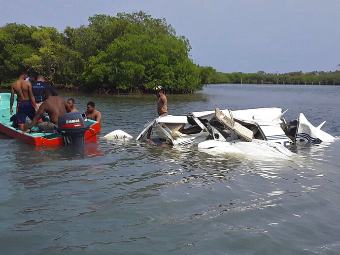 In this photo released by the Honduras Fire Department, firefighters and men work at the crash site of a plane that fell into the Atlantic in Roatan, Bay Island, Honduras, Saturday, May 18, 2019. All five people on board were killed after the plane plummeted shortly after takeoff from the popular tourist destination of Roatan en route to the port of Trujillo. (Honduras Fire Department via AP)