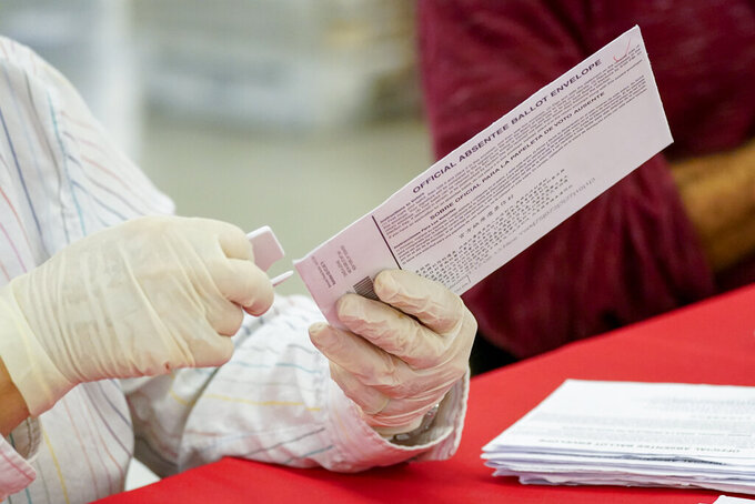 New York City Board of Election staff member removes an absentee ballot from the envelope as she helps count ballots in the primary election, Friday, July 2, 2021, in New York. (AP Photo/Mary Altaffer)