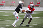 File-This Oct. 3, 2020, file photo shows Ohio State quarterback C.J. Stroud, left, handing the ball to running back Trey Sermon during their NCAA college football practice in Columbus, Ohio. The overarching question this spring is who will be starting at quarterback when the Buckeyes open the season on Sept. 2 at Minnesota. The early departure of Justin Fields for the NFL left two untested backups — pro-style quarterbacks Stroud and Jack Miller III, two of the top prep signal-callers in the country that Ohio State snagged in the 2020 recruiting class. (AP Photo/Jay LaPrete, File)