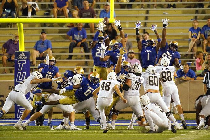 UC Davis' Isaiah Gomez (48) kicks the go-ahead field goal over the Tulsa defense during the second half of an NCAA college football game Thursday, Sept. 2, 2021, in Tulsa, Okla. (AP Photo/Sue Ogrocki)