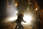 Anti-government protesters are sprayed by water form the riot police, during a protest near the parliament square, in downtown Beirut, Lebanon, Sunday, Dec. 15, 2019. Lebanese security forces fired tear gas, rubber bullets and water cannons Sunday to disperse hundreds of protesters for a second straight day, ending what started as a peaceful rally in defiance of the toughest crackdown on anti-government demonstrations in two months. (AP Photo/Hussein Malla)
