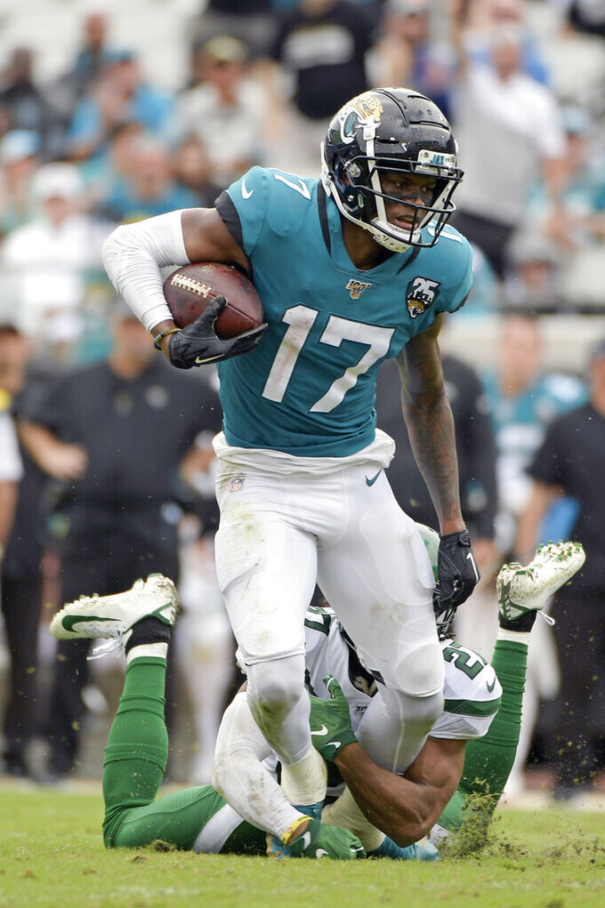 Jacksonville Jaguars wide receiver D.J. Chark (17) is stopped by New York Jets cornerback Darryl Roberts after a reception during the first half of an NFL football game, Sunday, Oct. 27, 2019, in Jacksonville, Fla. (AP Photo/Phelan M. Ebenhack)