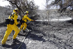Brett Palmer, left, Anthony Ayala with the South Placer Fire Dept. hose down hot spot from a wildfire Saturday, Oct. 12, 2019, in Porter Ranch, Calif.    (AP Photo/Marcio Jose Sanchez)
