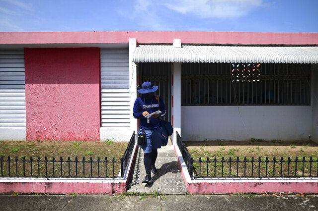 Postal worker Jose Montoya does his rounds in Carolina, Puerto Rico, Thursday, Oct. 1, 2020. More than half of all homes in Puerto Rico lack a physical address, so the absence of street names and numbers also have created multiple problems ranging from ambulances unable to reach a home in time to a delay in the distribution of aid after Hurricane Maria and a string of recent earthquakes. (AP Photo/Carlos Giusti)