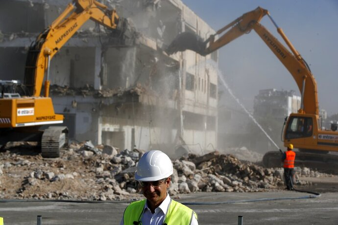 Greece's prime minister Kyriakos Mitsotakis wearing a helmet and plastic glasses stands at the old airport as bulldozers demolish an abandoned building in Athens, Friday, July 3, 2020. Mitsotakis inaugurated the start of construction work on a long-delayed major development project at the prime seaside site of the old Athens airport. The development of the 620-hectare (1,500-acre) Hellenikon site was a key element of the privatization drive that was part of Greece's international bailouts. (AP Photo/Thanassis Stavrakis)