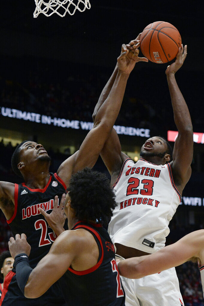 Western Kentucky center Charles Bassey (23) shoots against Louisville center Steven Enoch, top left, during the first half of an NCAA college basketball game Friday, Nov. 29, 2019, in Nashville, Tenn. (AP Photo/Mark Zaleski)