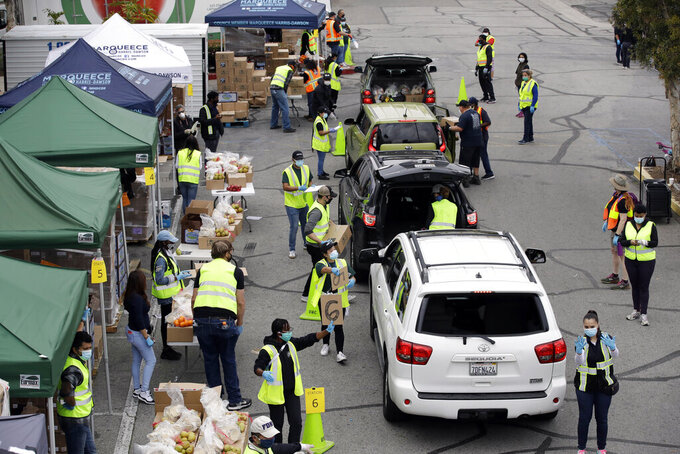 Food is loaded onto vehicles last a food distribution center Friday, April 17, 2020, in the Crenshaw district of Los Angeles. Food banks in the state have seen a spike in numbers as the state's unemployment level has jumped to to 5.3% for the month of March. (AP Photo/Marcio Jose Sanchez)