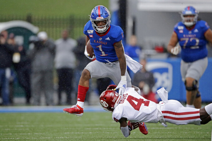 Kansas running back Pooka Williams Jr. (1) is tackled by Oklahoma cornerback Jaden Davis (4) during the first half of an NCAA college football game Saturday, Oct. 5, 2019, in Lawrence, Kan. (AP Photo/Charlie Riedel)