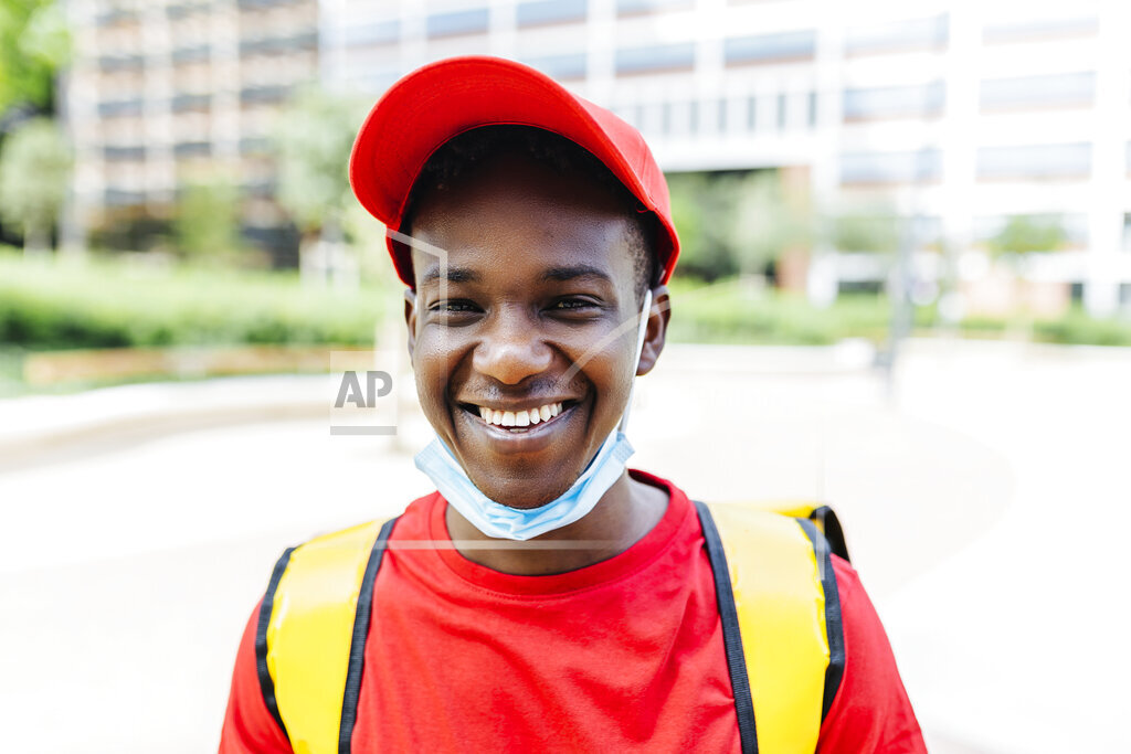 Smiling delivery man wearing red hat during COVID-19
