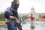 A Black Lives Matter activist carrying a semi-automatic rifle walks outside at the Capitol building in Frankfort, Ky., Wednesday, Jan 17, 2021. The Capitol, the Capitol complex, and surrounding grounds have been closed. (AP Photo/Bryan Woolston)
