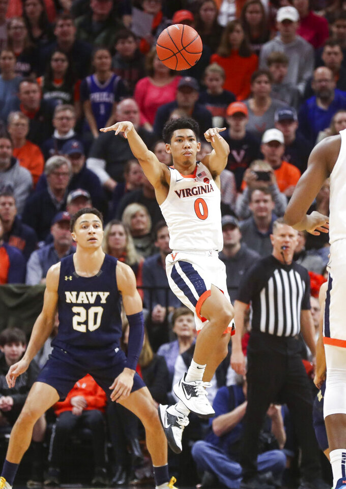 Virginia guard Kihei Clark (0) passes the ball next to Navy guard Greg Summers (20) during an NCAA college basketball game in Charlottesville, Va., Sunday, Dec. 29, 2019. (AP Photo/Andrew Shurtleff)