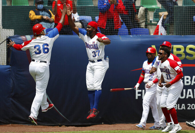Dominican Republic outfielder Johan Mieses, left, is congratulated by his teammates after he scored a run against Venezuela during a final Olympic baseball qualifier game, in Puebla, Mexico, Saturday, June 26, 2021. (AP Photo/Fernando Llano)