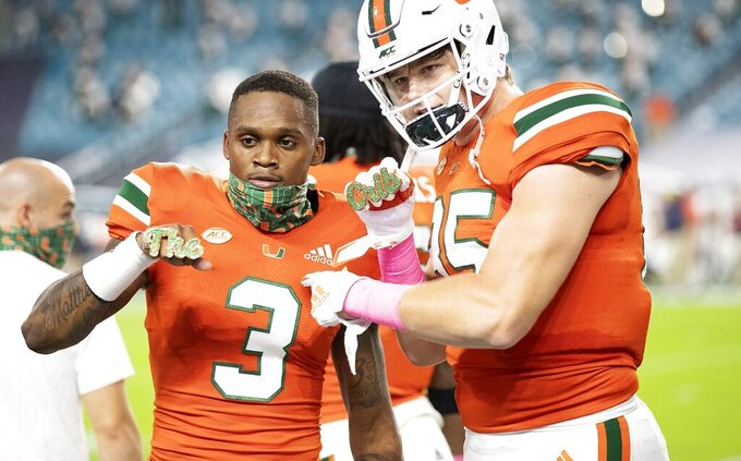 Miami wide receiver Mike Harley (3) and tight end Will Mallory (85) react after Harley's first-quarter touchdown against Virginia during an NCAA college football game in Miami Gardens, Fla., Saturday, Oct. 24, 2020. (Al Diaz/Miami Herald via AP)
