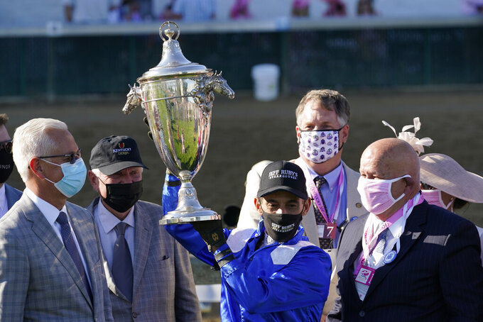 John Velazquez holds the trophy after riding Malathaat to victory during the 147th running of the Kentucky Oaks at Churchill Downs, Friday, April 30, 2021, in Louisville, Ky. (AP Photo/Brynn Anderson)