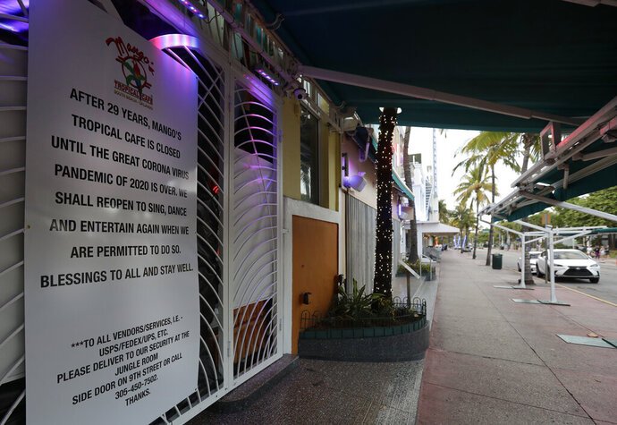 A sign is shown outside the closed Mango's Tropical Cafe along the normally bustling streets of the Art Deco district, Wednesday, March 25, 2020, in Miami Beach, Florida's famed South Beach. The new coronavirus causes mild or moderate symptoms for most people, but for some, especially older adults and people with existing health problems, it can cause more severe illness or death.(AP Photo/Wilfredo Lee)