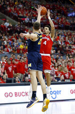 Ohio State guard Duane Washington, right, goes up for a shot in front of Michigan guard Franz Wagner during the second half of an NCAA college basketball game in Columbus, Ohio, Sunday, March 1, 2020. Ohio State won 77-63. (AP Photo/Paul Vernon)