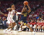 West Virginia guard Oscar Tshiebwe (34) goes up for a shot ahead of Oklahoma forward Kristian Doolittle (21) during the first half of an NCAA college basketball game in Norman, Okla., Saturday, Feb. 8, 2020. (AP Photo/Kyle Phillips)