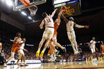 Texas center Will Baker drives to the basket between Iowa State's Michael Jacobson (12) and Tre Jackson (3) during the second half of an NCAA college basketball game, Saturday, Feb. 15, 2020, in Ames, Iowa. Iowa State won 81-52. (AP Photo/Charlie Neibergall)