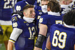 Notre Dame quarterback Ian Book (12) celebrates with offensive lineman Robert Hainsey (72) and offensive lineman Tommy Kraemer (78) after Notre Dame defeated Syracuse in an NCAA college football game Saturday, Dec. 5, 2020, in South Bend, Ind. (Matt Cashore/Pool Photo via AP)