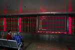Chinese women chat with each other near an electronic screen displaying stock prices at a brokerage house in Beijing, Friday, Dec. 6, 2019. Shares swung higher in Asia on Friday after a wobbly day of trading on Wall Street as investors awaited a U.S. government jobs report and kept an eye out for developments in China-U.S. trade talks. (AP Photo/Andy Wong)