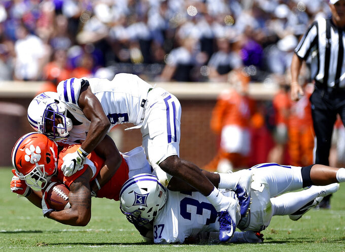 Clemson's Amari Rodgers is tackled after catching a pass, by Furman's Aaquil Annoor, top, and Davonta Porter during the first half of an NCAA college football game Saturday, Sept. 1, 2018, in Clemson, S.C. (AP Photo/Richard Shiro)