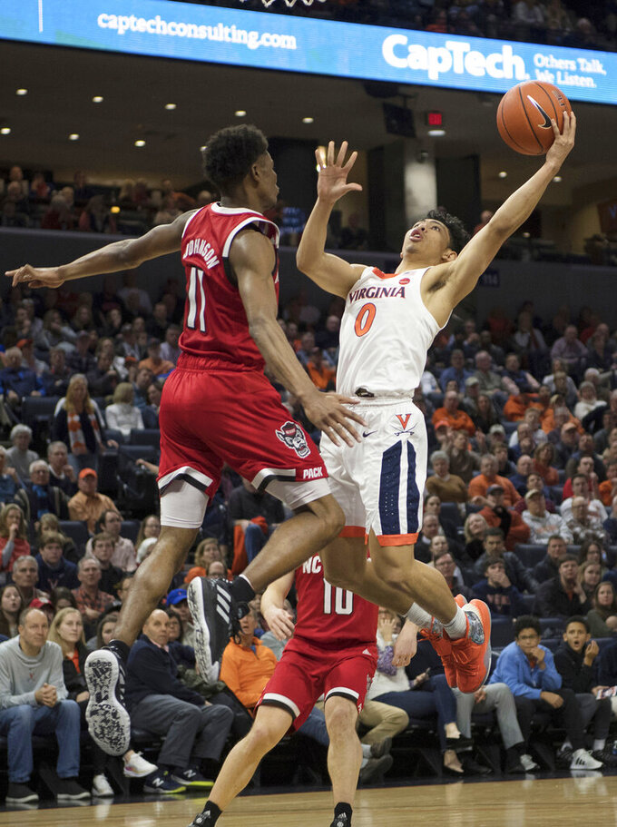 Virginia guard Kihei Clark (0) drives to basket as North Carolina State guard Markell Johnson (11) defends play during the second half of an NCAA college basketball game in Charlottesville, Va., Monday, Jan. 20, 2020. (AP Photo/Lee Luther Jr.)
