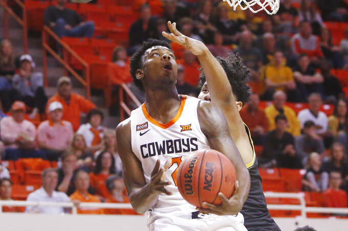 Oklahoma State guard Chris Harris Jr., left, goes to the basket in front of Wichita State forward Isaiah Poor Bear-Chandler, right, in the first half of an NCAA college basketball game in Stillwater, Okla., Sunday, Dec. 8, 2019. (AP Photo/Sue Ogrocki)