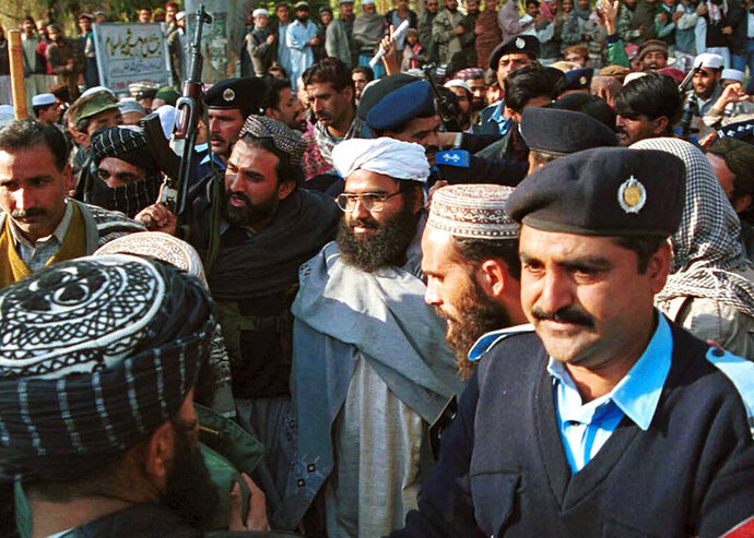 FILE - In this Jan. 27, 2000 file photo, Masood Azhar, center, wearing glasses and white turban, leader of Jaish-e-Mohammad arrives in Islamabad, Pakistan. In 2019, the United Nations added Azhar to its blacklist after several unsuccessful attempts. Pakistan got a mixed review for its efforts to curb terrorist financing and money laundering as it tries to avoid being blacklisted by the Financial Action Task Force, a global watchdog, when it meets in Paris Wednesday, Oct. 16, 2019. (AP Photo/Mian Khursheed, File)