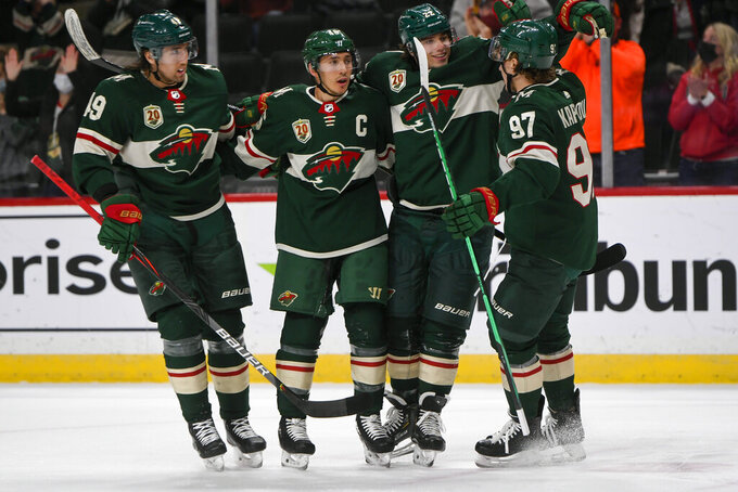 Minnesota Wild center Victor Rask, defenseman Jared Spurgeon, left wing Kevin Fialaand left wing Kirill Kaprizov, from left, celebrate after Spurgeon scored a goal against the Anaheim Ducks with an assist from Kaprizov during the first period of an NHL hockey game Saturday, May 8, 2021, in St. Paul, Minn. (AP Photo/Craig Lassig)