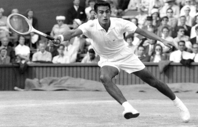 """FILE - Alex Olmedo makes a return as he plays against Roy Emerson, of Australia, during a men's singles semifinal match at the all England Lawn Tennis Championship at Wimbledon, London, in this July 1, 1959, file photo. Olmedo, who won the Wimbledon and Australian Championships singles titles in 1959 and was inducted into the International Tennis Hall of Fame in 1987, has died. He was 84. Citing Olmedo's son, Alejandro Jr., the Hall of Fame said Thursday that Olmedo died of brain cancer on Wednesday, Dec. 9, 2020. Alejandro """"Alex"""" Olmedo was born in Peru in 1936 and moved to the United States as a teenager. (AP Photo/Leslie Priest, File)"""