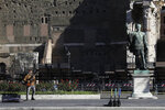 A street musician performs with his electric guitar beside the statue of Roman Emperor Julius Cesar on a almost empty Via Dei FOri Imperiali avenue in Rome, Wednesday, Oct. 28, 2020. Italy on Tuesday registered nearly 22,000 confirmed COVID-19 infections since the previous day, its highest one-day total so far in the pandemic. The day-to-day increase in confirmed deaths also jumped, to 221, according to Health Ministry figures. (AP Photo/Gregorio Borgia)