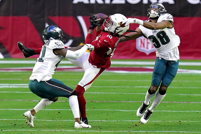 Arizona Cardinals wide receiver DeAndre Hopkins (10) pulls in a catch as Philadelphia Eagles defensive back Michael Jacquet (38) and cornerback Kevon Seymour (41) defend during the first half of an NFL football game, Sunday, Dec. 20, 2020, in Glendale, Ariz. (AP Photo/Ross D. Franklin)