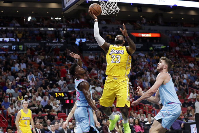 Los Angeles Lakers forward LeBron James (23) shoots over Miami Heat forward Jimmy Butler (22) and forward Meyers Leonard, right, during the first half of an NBA basketball game, Friday, Dec. 13, 2019, in Miami. (AP Photo/Lynne Sladky)