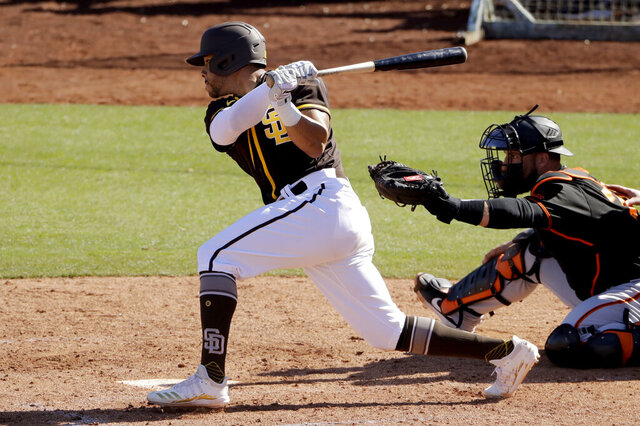 San Diego Padres' Tommy Pham hits an RBI single during the fifth inning of a spring training baseball game against the San Francisco Giants Sunday, March 1, 2020, in Peoria, Ariz. (AP Photo/Charlie Riedel)