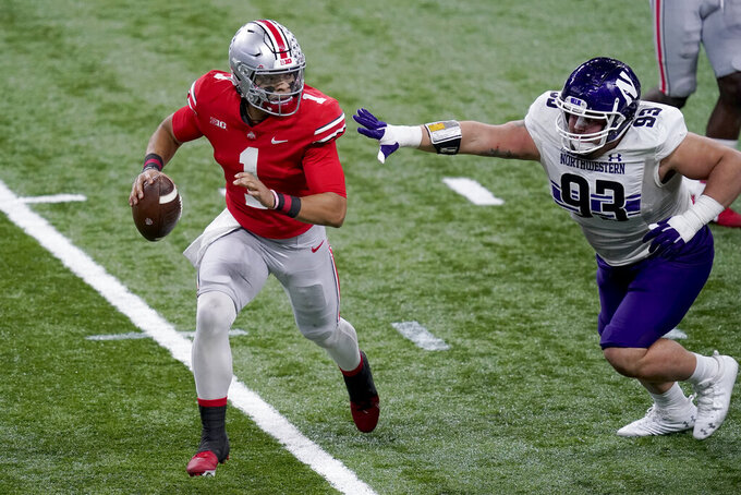 Ohio State quarterback Justin Fields (1) scrambles away from Northwestern defensive lineman Joe Spivak (93) during the first half of the Big Ten championship NCAA college football game, Saturday, Dec. 19, 2020, in Indianapolis. (AP Photo/Darron Cummings)