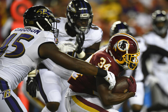 Washington Redskins running back Byron Marshall (34) carries the ball despite pressure from Baltimore Ravens linebacker Jaylon Ferguson (45) during the first half of an NFL preseason football game at FedEx Field in Landover, Md., Thursday, Aug. 29, 2019. (AP Photo/Susan Walsh)