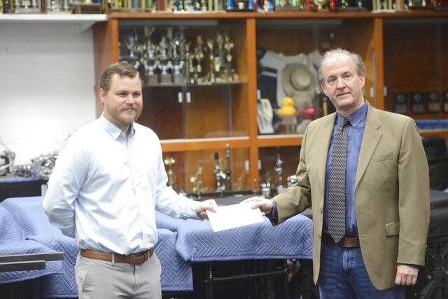 In this Thursday, May 14, 2020 photo, Charles Womack, right, delivers a check for $50,000 from the Womack Foundation to George Washington High Schools director of bands Cody Kesling in the school's band room in Danville, Va. (Parker Cotton/Danville Register & Bee via AP)
