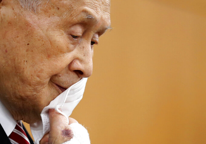 FILE - In this Feb. 4, 2021, file photo, Yoshiro Mori, the president of the Tokyo Olympic Organizing Committee, takes off his protective face mask as he attends a news conference in Tokyo. Mori — a former prime minister — stepped down after making derogatory comments about women. (Kim Kyung-hoon/Pool Photo via AP, File)