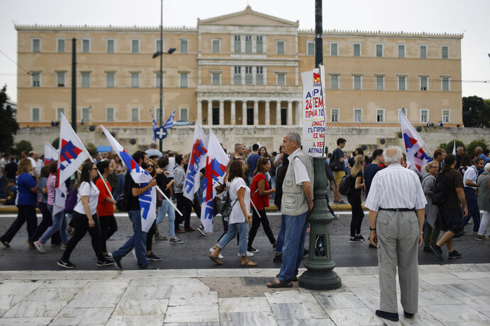 Protesters from Communist-affiliated PAME labor union march during a 24-hour strike in front of the parliament in central Athens, Tuesday, Sept. 24, 2019. Greek island ferries were moored in port, many Athens public transport services were shut down and state hospitals functioned on emergency staffing due to Tuesday's strike by Greek unions against draft legislation that would make it harder for unions to call strikes in the future. (AP Photo/Petros Giannakouris)