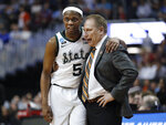 FILE - In this March 29, 2019, file photo, Michigan State guard Cassius Winston (5) puts his arm around coach Tom Izzo following the team's 80-63 win over LSU in an NCAA men's college basketball tournament East Region semifinal, in Washington. Winston has joined a select group of players in program history as an All-America player and Big Ten player of the year. If he can help the Spartans win two more games, he'll join Magic Johnson and Mateen Cleaves as the school's national championship-winning point guards. (AP Photo/Patrick Semansky, File)