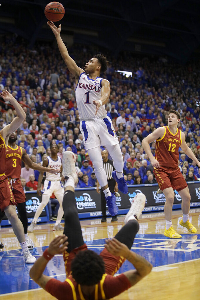 Kansas guard Devon Dotson (1) makes a basket after getting past Iowa State guard Prentiss Nixon, bottom, during the first half of an NCAA college basketball game in Lawrence, Kan., Monday, Feb. 17, 2020. (AP Photo/Orlin Wagner)