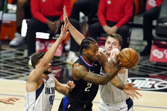 Los Angeles Clippers forward Kawhi Leonard (2) passes the ball from between Dallas Mavericks forward Maxi Kleber, left, and guard Luka Doncic during the first half in Game 2 of an NBA basketball first-round playoff series Tuesday, May 25, 2021, in Los Angeles. (AP Photo/Marcio Jose Sanchez)