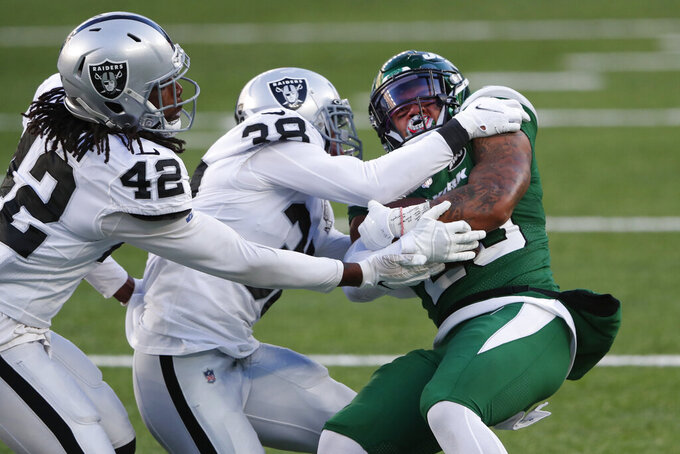 Las Vegas Raiders defense tackle New York Jets' Ty Johnson, right, during the second half an NFL football game, Sunday, Dec. 6, 2020, in East Rutherford, N.J. (AP Photo/Noah K. Murray)