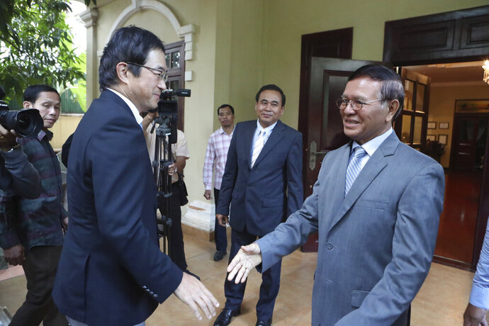 Japanese Ambassador Masahiro Mikami, front left, shakes hands with the banned Cambodia National Rescue Party's President Kem Sokha before a meeting at his house in Phnom Penh, Cambodia, Wednesday, Nov. 13, 2019. Kem Sokha was freed Sunday by court order after more than two years in detention without trial. (AP Photo/Heng Sinith)