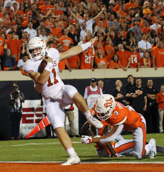 FILE - In this Oct. 27, 2018, file photo, Texas quarterback Sam Ehlinger (11) scores a touchdown after escaping from Oklahoma State safety Kenneth Edison-McGruder in the first half of an NCAA college football game, in Stillwater, Okla. Texas has a rising star in quarterback Sam Ehlinger who will get some attention for the Heisman Trophy if he can duplicate his impressive 2018 season when he passed for 25 touchdowns and ran for 16 more. (AP Photo/Brody Schmidt, File)