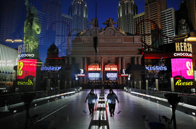 """FILE - In this April 18, 2020, file photo, a lone worker wearing a mask cleans a pedestrian walkway devoid of the usual crowds as casinos and other business are shuttered due to the coronavirus outbreak in Las Vegas. Workers in the key Las Vegas restaurant, hospitality and casino industry can now get a coronavirus vaccine. State COVID-19 response officials issued a statement Thursday, March 11, 2021, immediately adding """"Frontline Commerce and Service Industries"""" in Clark County to the eligibility list. (AP Photo/John Locher, File)"""