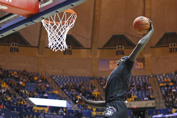Oklahoma State forward Yor Anei (14) goes to the basket during the first half of the team's NCAA college basketball game against West Virginia Tuesday, Feb. 18, 2020, in Morgantown, W.Va. (AP Photo/Kathleen Batten)